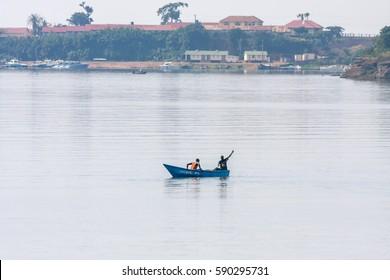 ENTEBBE, UGANDA - JANUARY 10, 2008: Fishermen in wooden boat moves in Victoria Lake bay against hazy bank on January 10, 2008 in Entebbe.