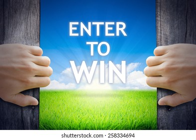 Enter to WIN. Hand opening an old wooden door and found Enter to WIN word floating over green field and bright blue Sky Sunrise.
