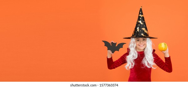 Enter at your own risk. Halloween child happy smile orange background. Witch child hold bat and pumkin. Little child wear witch hat and hair. Small child with Halloween look, copy space.
