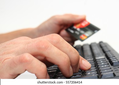 Entering payments online using a keyboard and a credit card on a white background