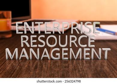 Enterprise Resource Management - letters on wooden desk with laptop computer and a notebook. 3d render illustration.