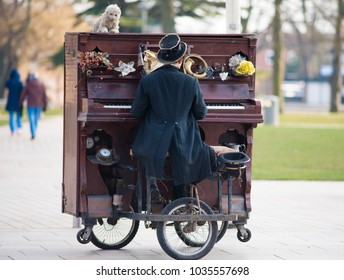 entertainer in Victorian coat tails and top hat playing upright moveable piano on wheels in street