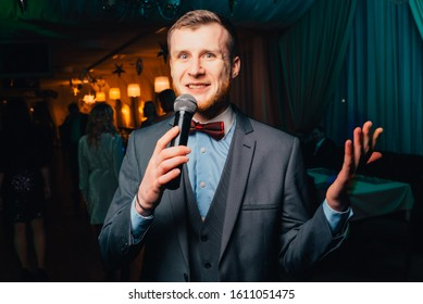 The entertainer. Young elegant talking man holding microphone