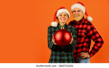 Entertainment ideas for adults. Santa team. Loving couple orange background. Christmas magical time. We love christmas. Couple in love enjoy christmas holiday celebration. Family wear santa hats.