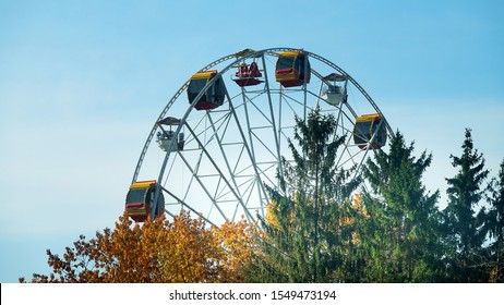 Entertainment industry for sunday holiday rides. Ferris wheel for citizens and guests, big wheel metal construction. Bright Sunny weekend in the city
