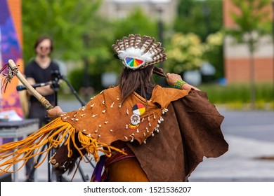 Entertainment at multicultural festival. A woman dressed in traditional indigenous attire, dancing with sacred objects during an outdoor gig celebrating native culture.