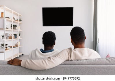 Entertainment. Rear back view of black young family of two watching tv, sitting on sofa, looking at blank television screen on the wall with isolated empty monitor for mockup, banner, copy space