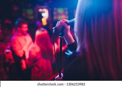 Entretenimiento en una boda. Una cantante interactúa con la multitud mientras un hombre toca una guitarra acústica.