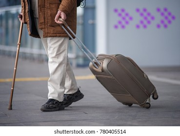 Enthralling trip. Close up of male legs going with luggage along airport building with walking stick