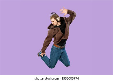 Enthusiastic black man posing emotionally on purple backgrond. Indoor photo of good-looking african guy in sport shoes jumping in studio.          - Image