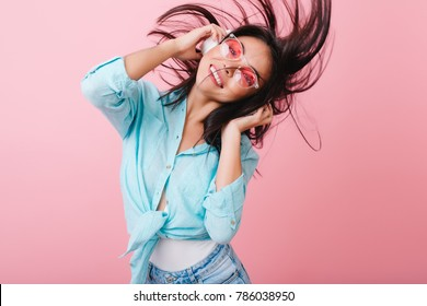 Enthusiastic brunette girl dancing with hair waving during photoshoot in studio with pink interior. Indoor photo of active hispanic woman in headphones and sunglasses having fun.