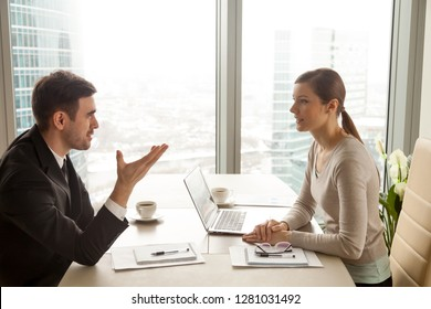 Enthusiastic businessman and businesswoman discussing company business, talking about new project, sharing ideas during meeting sitting at office desk near big window with urban cityscape, side view