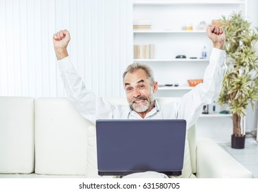 enthusiastic businessman with an open laptop sitting on sofa in modern office.