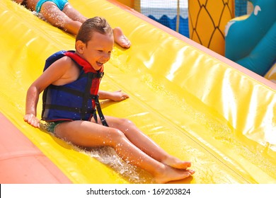 Enthusiastic children on slide in the waterpark
