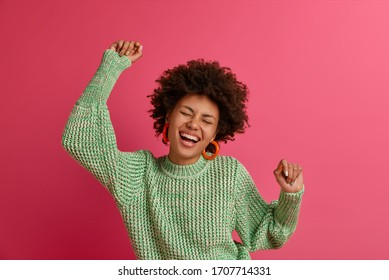 Enthusiastic dark skinned woman moves with rhythm of music, keeps arms up, enjoys awesome party or festival, dressed in knitted jumper, tries to foreget about everyday problems, has fun, poses indoor