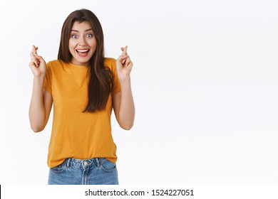 Enthusiastic, excited attractive woman in yellow t-shirt, hold fingers crossed and smiling with anticipation in eyes, believe dreams come true, making wish, anticipating important results hopeful