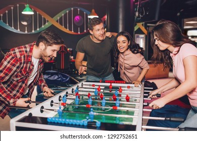 Enthusiastic excited young man and woman playing table soccer in room. Their friends stand beside and cheer.