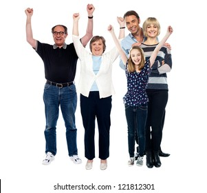 Enthusiastic family rejoicing with raised arms. Three generations portrait.