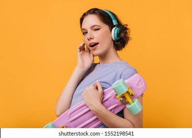 Enthusiastic female model in big blue headphones playfully posing with longboard. Charming girl with skateboard smiling on bright yellow background.