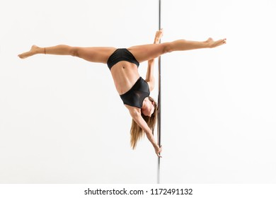 Enthusiastic female pole dancer with legs apart training over white background