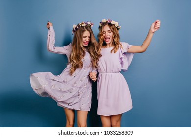 Enthusiastic girl in flower wreath fooling around with sister on blue background. Indoor photo of glad ladies in trendy dresses dancing together.