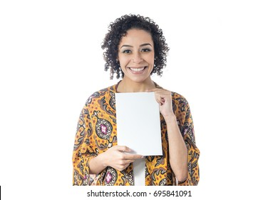 Enthusiastic girl is holding a blank paper with room for text. Short and curly haired woman wears yellow clothes and with floral pattern. Summer and tropical concept.
