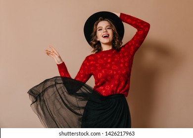 Enthusiastic girl touching hat with smile. Studio shot of excited caucasian woman dancing on brown background.