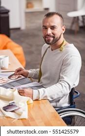 Enthusiastic handicapped dressmaker reading fashion magazines