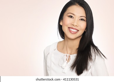 Enthusiastic happy smiling attractive casual thirty to forty year old Asian woman posing in studio.