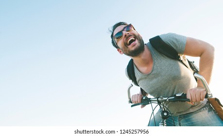 Enthusiastic hipster guy with retro sunglasses having outdoor fun and riding a bicycle. Active sport man with excited face expression exploring and traveling by mountain bike on the road.