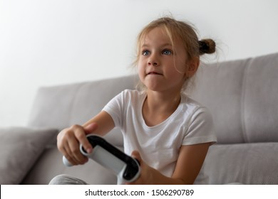 Enthusiastic kid in casual outfit playing with joystick while sitting on sofa in living-room