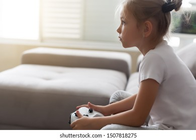 Enthusiastic kid in casual outfit playing with joystick while sitting on sofa in livingroom