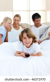 Enthusiastic little boy holding a remote  lying on the bed
