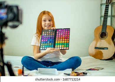 enthusiastic little caucasian blogger show decorative cosmetics at camera, girl do make-up at home, she enjoy being beauty blogger