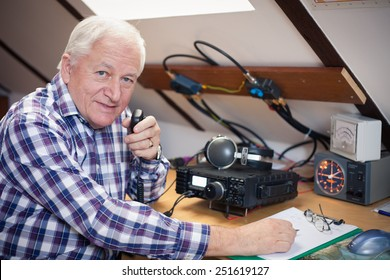 Enthusiastic middle-aged radio-amateur at his station