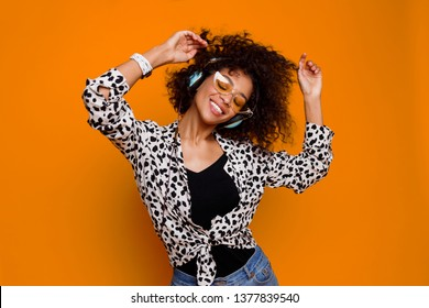 Enthusiastic mix race woman listening favorite music by earphones and dancing over orange background. Indoor black girl with close eyes  posing in studio.