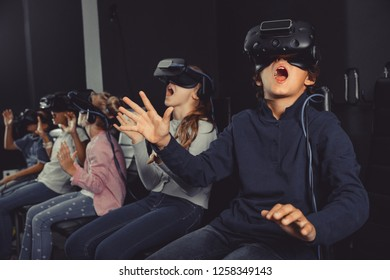Enthusiastic positive  children in virtual reality glasses in quest room