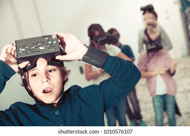 Enthusiastic  positive smiling children in virtual reality glasses in quest room