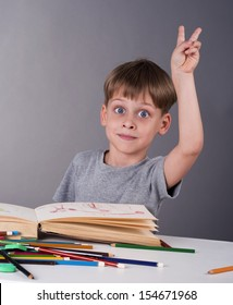 enthusiastic schoolboy raising his hand to give an answer, education concept