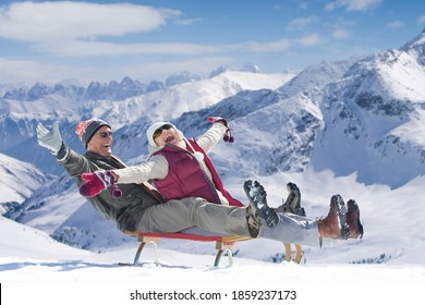 An Enthusiastic senior couple sledding down the slope with their arms outstretched on a snowy mountain
