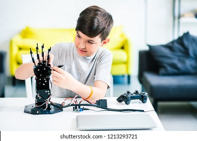 Enthusiastic smart boy sitting at the table while experimenting with robotic hand and preparing for engineering classes