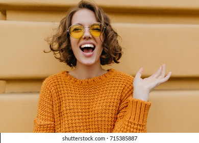 Enthusiastic smiling girl with shiny curls posing in front of old wall. Close-up outdoor portrait of enchanting lady in sweater and trendy glasses.