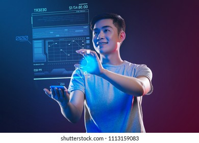 Enthusiastic web developer. Positive emotional web developer feeling happy while standing in his modern office with a tiny gadget in his hand and making a holographic image