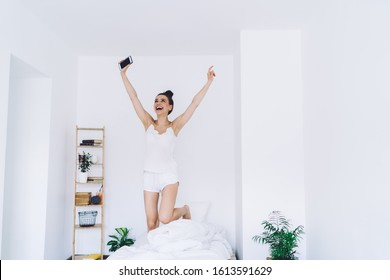 Enthusiastic woman in nightwear bouncing on comfortable bed with raised hands while using smartphone in room with minimalist interior and looking up