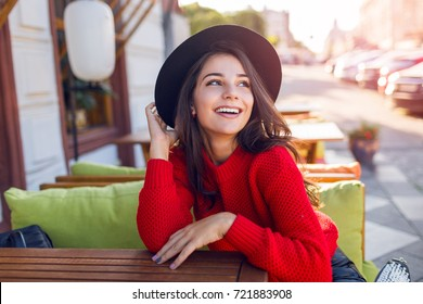 Enthusiastic Woman in trendy autumn outfit chilling in cozy cafe, looking around , happy emotions. Traveling woman.
