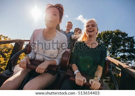 Enthusiastic young friends on roller coaster ride. Young people having fun at amusement park.