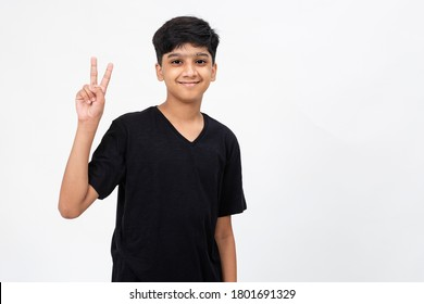 Enthusiastic young India boy raises his fingers showing victory sign. Cute teenager raising his arms in delight