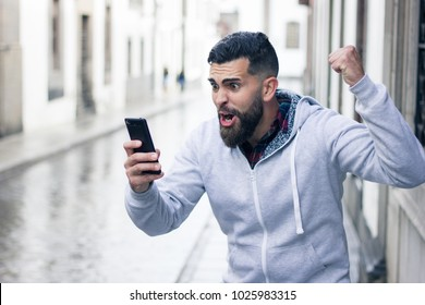 Enthusiastic young man looking at cellphone with victorious expression in the city. Overexcited hipster with grey hoodie holding mobile device and fist up. Online bet winner concept