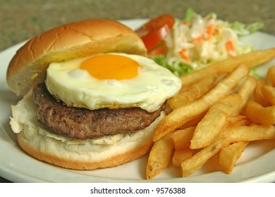 An enticing shot of hamburger with egg,fries and coleslaw.