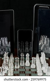Entire glass chess set on glass chess board with two tablets and smart phone positioned to show reflections.